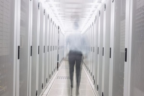 Blurred technician walking to the camera in a large data center